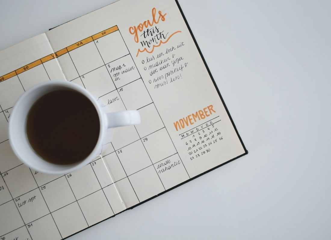Goal planner with a mug of coffee sitting on it
