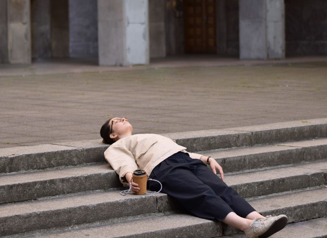 Tired person laying on staircase with coffee cup