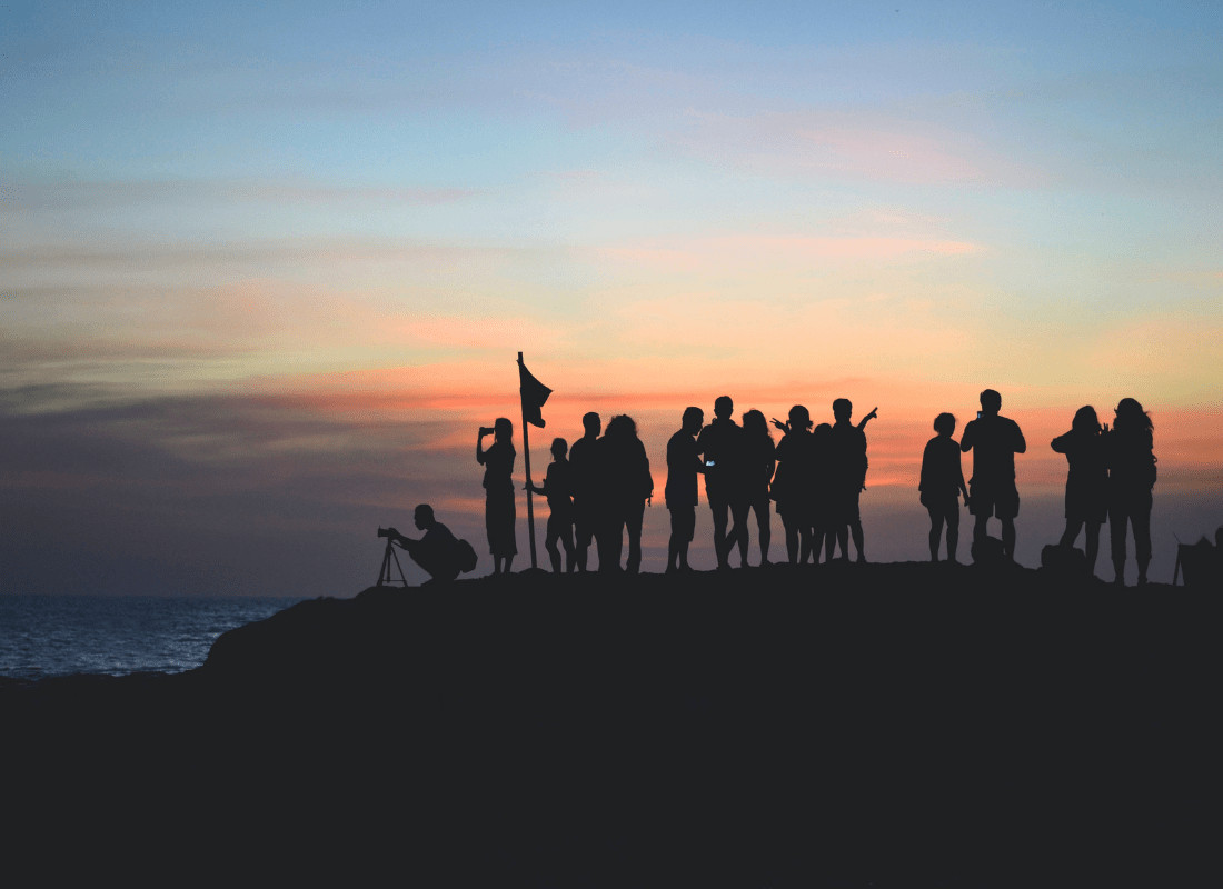 United team standing on mountain at sunset