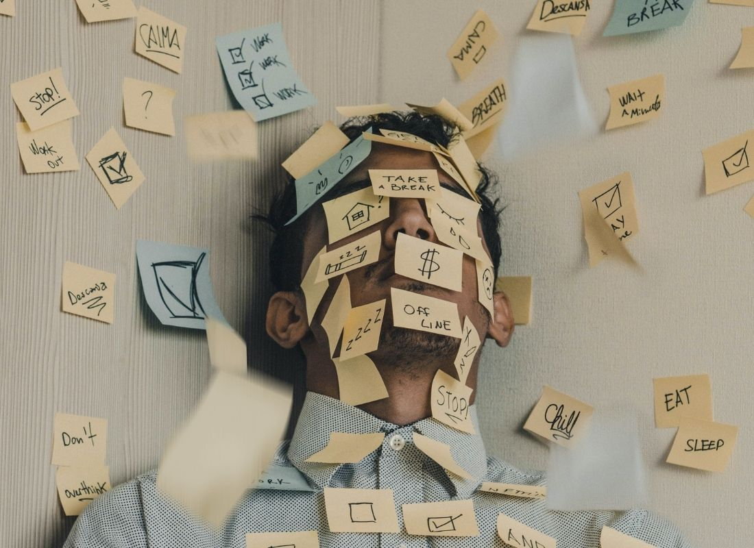 stressed man in corner with sticky notes on face