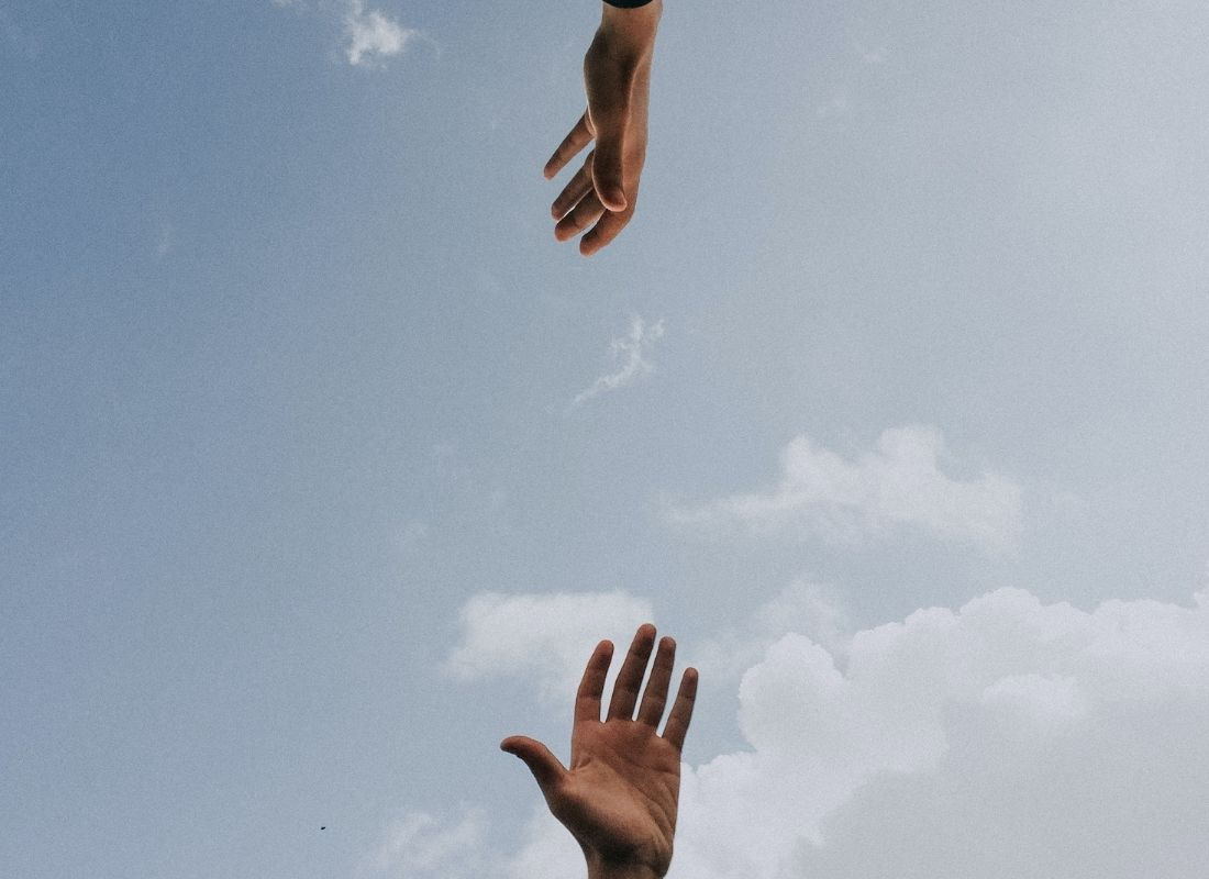 blue sky with two hands reaching for each other