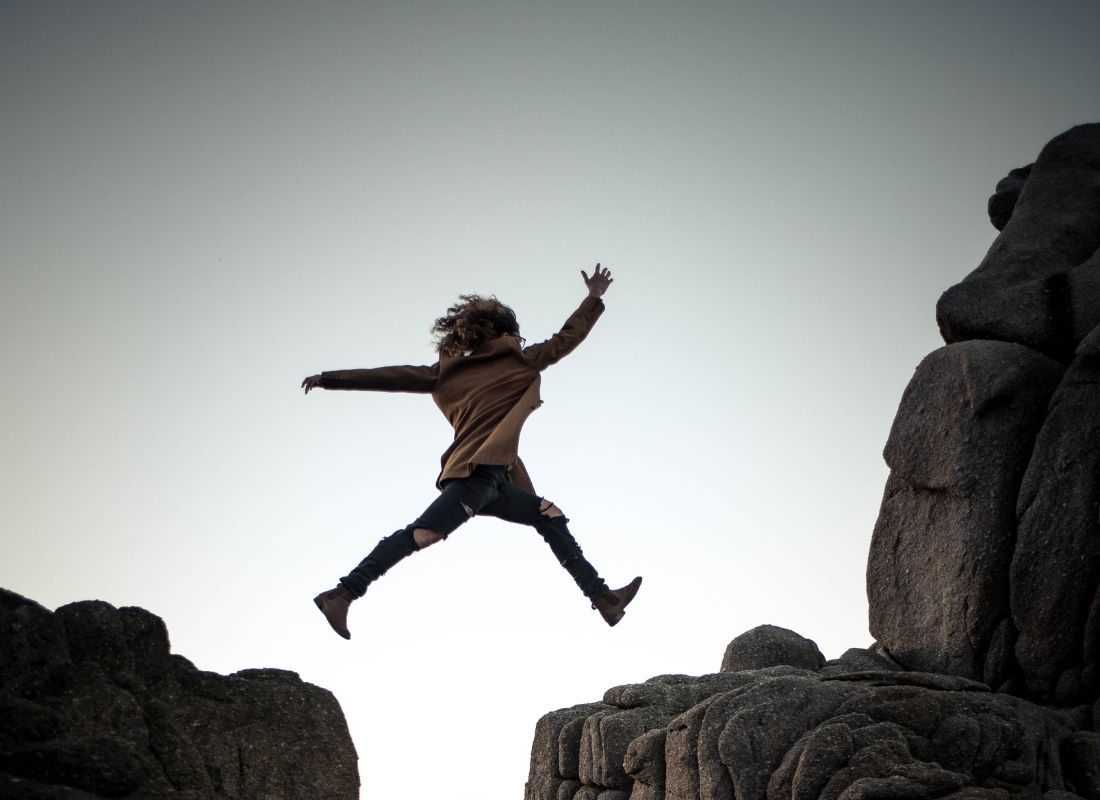 Woman conquering fear and jumping across rock cliffs