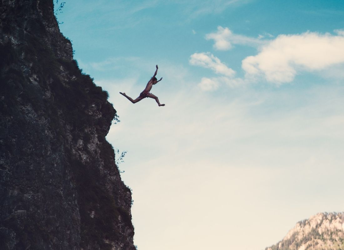 man jumping off cliff to conquer fears