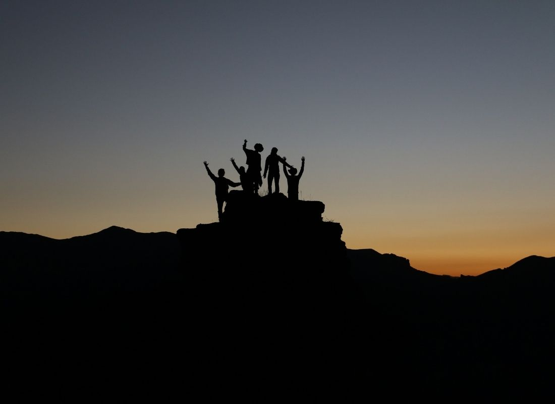 Successful team of hikers on top of a mountain at dusk