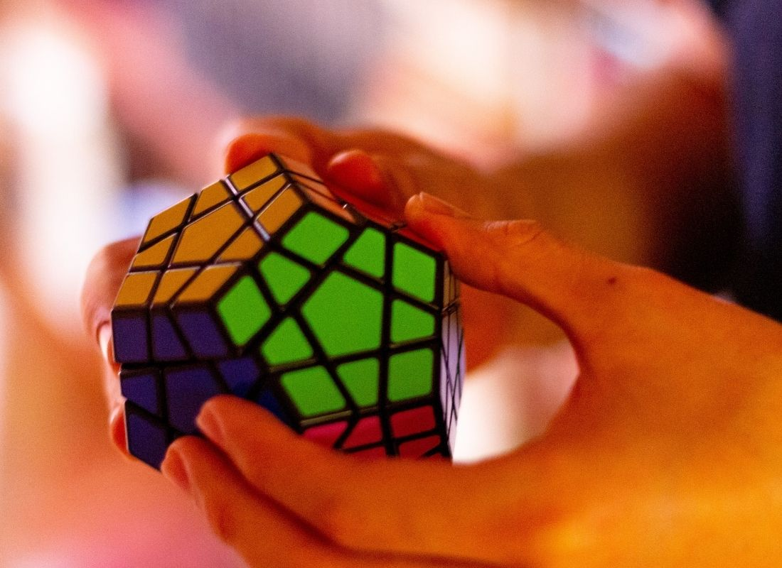 Person holding hexagonal colored Rubix cube and solving puzzle