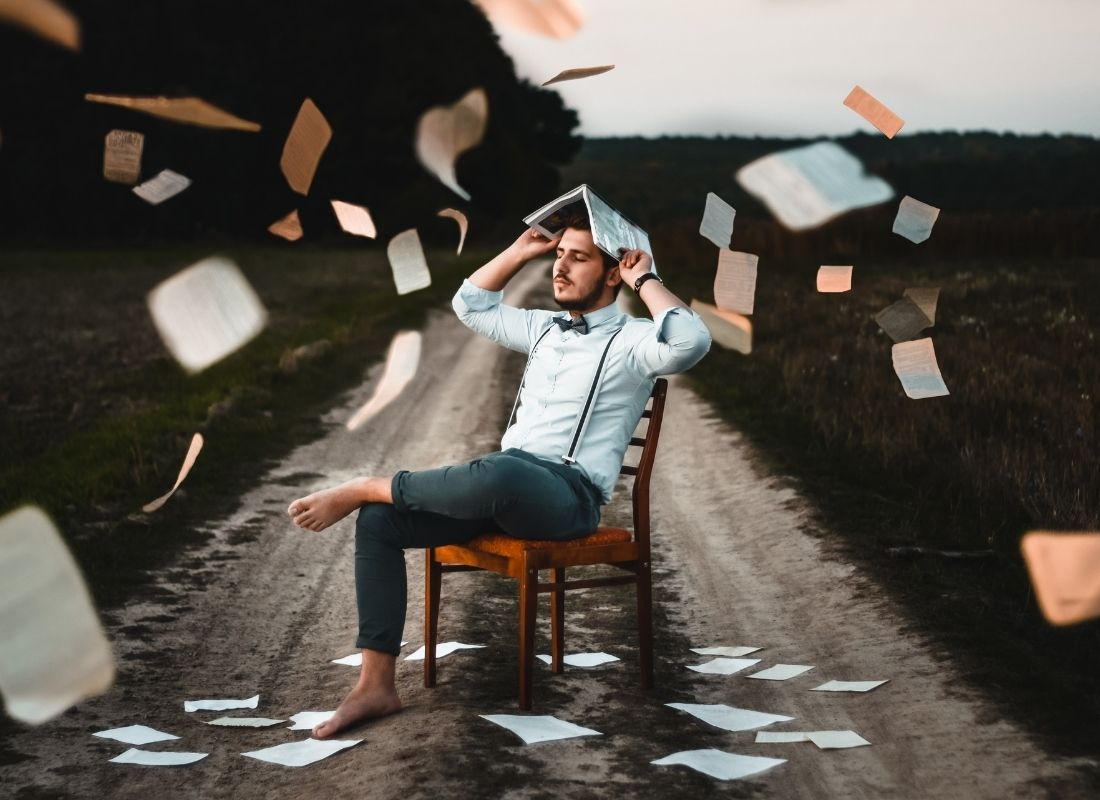 Man on chair on a road with papers falling around him