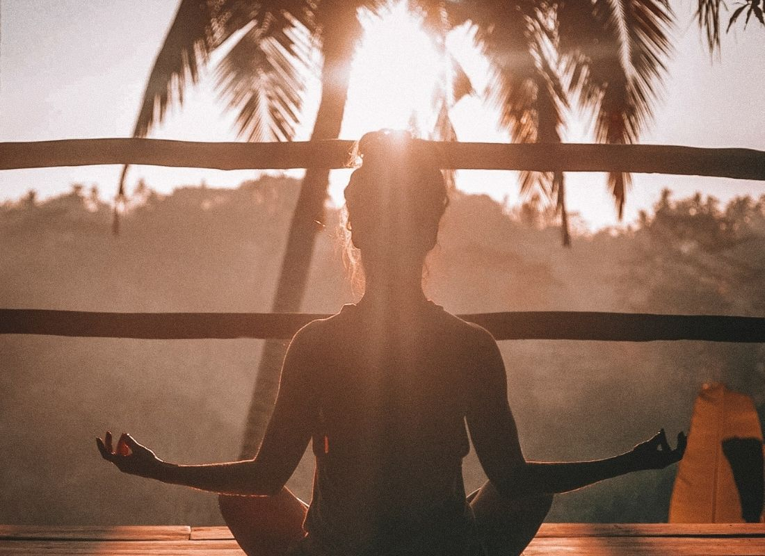 Woman sitting and visualizing her future in meditation at sunset